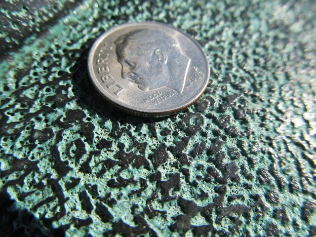 1.6.3 Detailed photograph of surface pitting on historic  bronze sculpture.